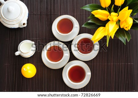 Tea set on a bamboo mat with yellow tulips and yellow candle in the form of eggs - stock photo