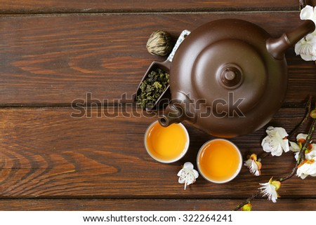 tea set (teapot, cups and different green tea) a wooden background, top view - stock photo