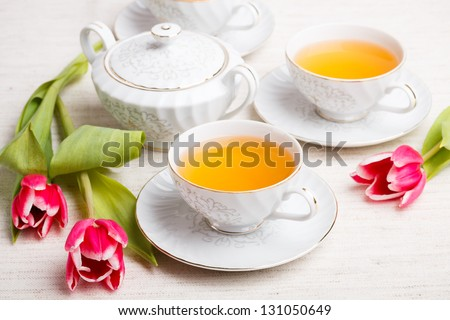 Tea set with flowers on canvas tablecloth