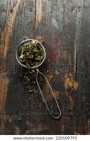 Tea stainer with aromatic herbal tea on wooden table background  - stock photo