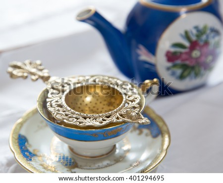 Tea strainer and cup of tea. - stock photo