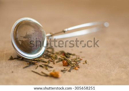 tea strainer with tea - stock photo