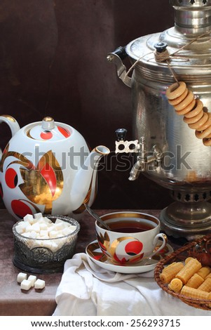 Tea submitted with wafer tubules and sugar and a samovar - stock photo