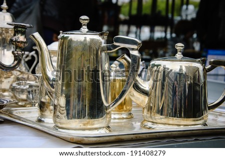 Tea time concept. Old metal teapots for sale at flea market in Paris (France). Reflection, light and shadow game. - stock photo