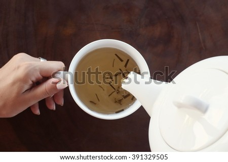 Tea time. Girl holding a cup of tea on the table - stock photo
