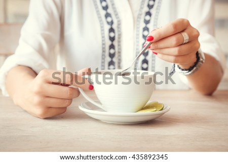 Tea time. Girl in cafe with cup of tea - stock photo