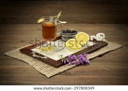 Tea Time Scene In The  Rustic Style. Glass Teacup With Lime Tree Herbal Green Tea, blueberries,  lemon, Herbs Leafs In The Basket,  Vintage Spoon On The Rough Old Wooden Table - stock photo