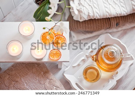 Tea-tray with hot grass drink, knitting clothes, dry oranges, candles and flowers. Winter mood. Cozy style - stock photo