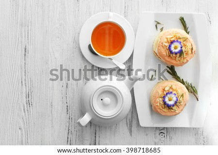 Tea with cakes on wooden background, top view - stock photo