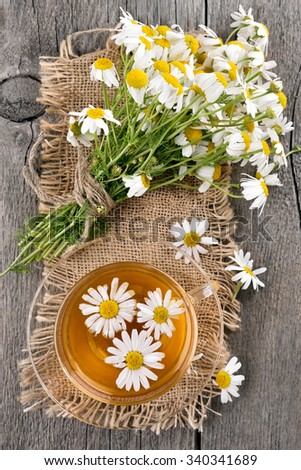 Tea with chamomile in glass cup on wooden table, top view - stock photo