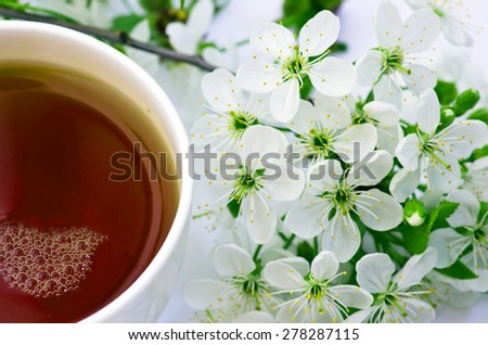 tea with cherry flowers and branches on white table, top view - stock photo