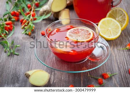 Tea with fresh goji berries and ginger - stock photo