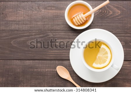 Tea with lemon and honey on the wooden background. - stock photo