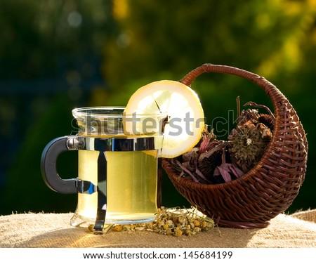 Tea with lemon near basket with dried flower - stock photo