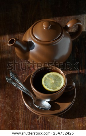 Tea with lemon. Tableware from dark ceramics. Cup of tea and teapot on old wooden table. top view - stock photo