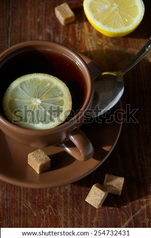 Tea with lemon. Tableware from dark ceramics. Cup of tea on an old wooden table. - stock photo