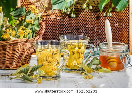 Tea with lime and honey served in the garden - stock photo