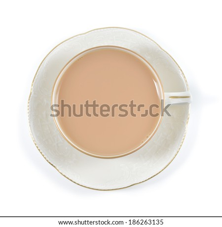 Tea with milk in antique porcelain cup isolated on white background. Porcelain cup and saucer with delicate relief structures and gold decoration. - stock photo