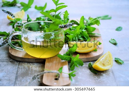 tea with mint and lemon on a vintage background - stock photo