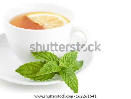 Tea with piece of lemon and mint on a plate over white background - stock photo
