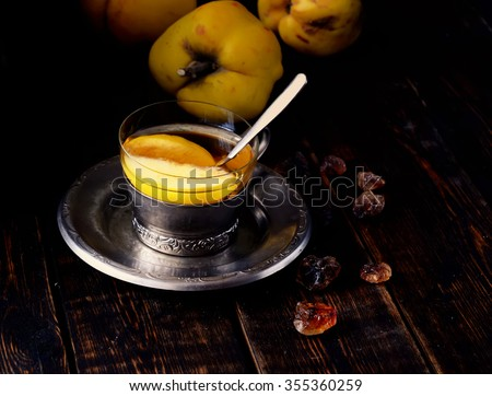 tea with quince, quince fruits on wooden background