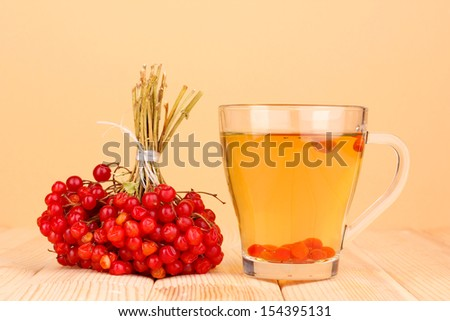 tea with red viburnum on table on beige background - stock photo