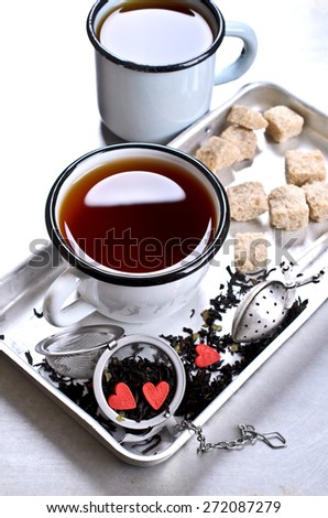 Tea with sweets in the shape of a heart against a metal strainer