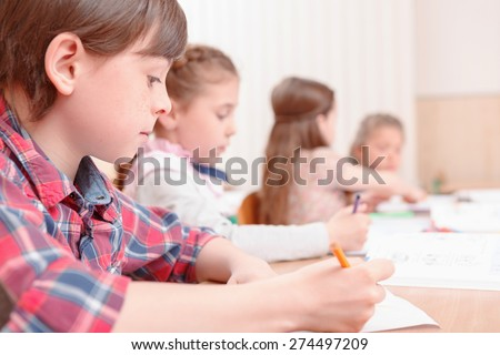 Teach to write. Pupils sitting at desk and studding side by side. - stock photo