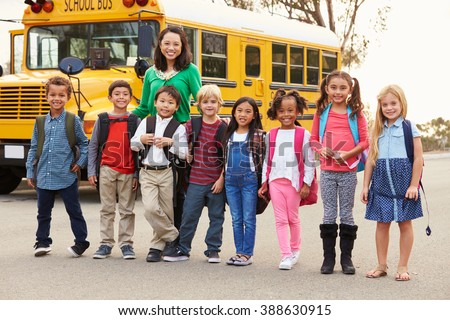 Teacher and a group of elementary school kids at a bus stop - stock photo