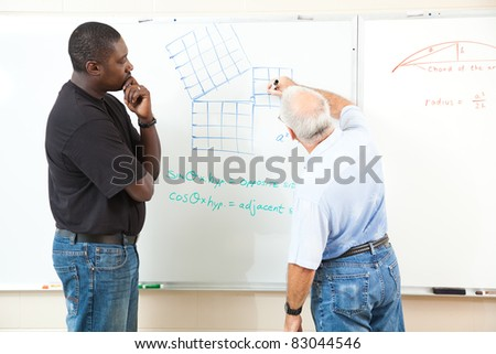 Teacher and adult student at the board working trigonometry equations.  Focus on the equations on the board. - stock photo