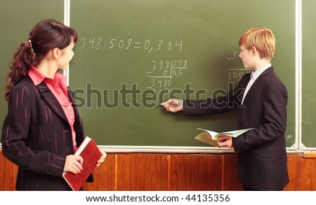 Teacher and boy at blackboard - stock photo