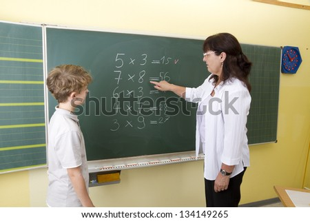 Teacher and boy in front of blackboard at school. - stock photo