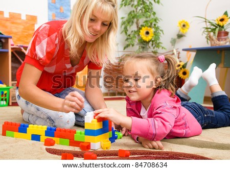 Teacher and child are playing with building bricks in preschool - stock photo