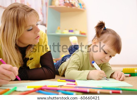 Teacher and child draw with felt-tip pens in preschool - stock photo