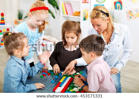Teacher and children are playing a board game in the classroom - stock photo