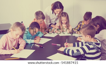 Teacher and elementary age children drawing at classroom in school