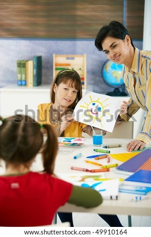 Teacher and elementary age schoolgirl showing colorful paining to classmate in art class in primary school classroom. - stock photo