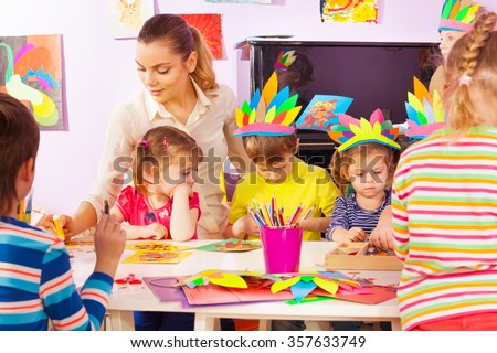 Child painting easel school teacher help stock photo for Group craft projects for adults