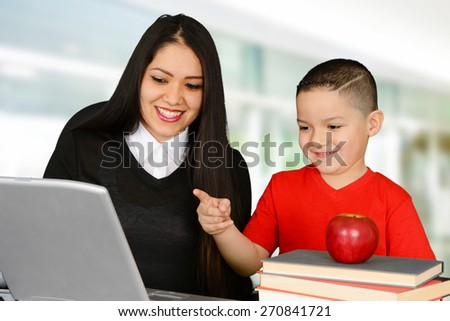 Teacher and her pupil looking at laptop - stock photo