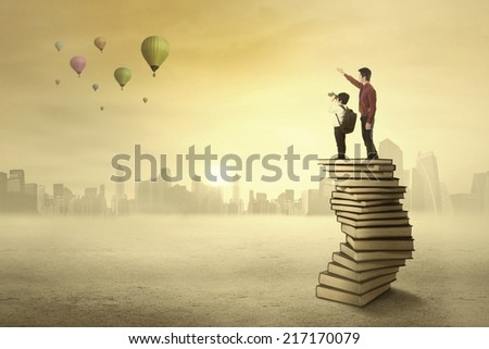 Teacher and his student standing on a pile of books looking at air balloon on the sky - stock photo