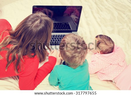 teacher and kids looking at laptop, early education and technology - stock photo