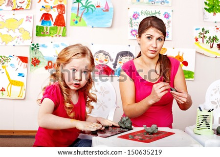 Teacher and little girl  playing with  clay. - stock photo