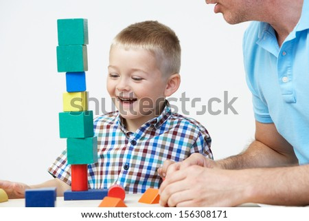 Teacher And Pre-School Pupil Playing With Wooden Blocks - stock photo