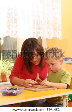 teacher and preschooler playing with wooden blocks - stock photo