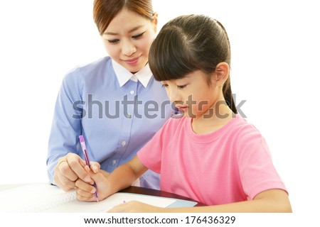 Teacher and pupil in classroom learning together. - stock photo