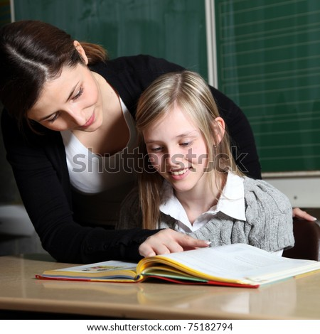 Teacher and pupil in classroom learning together. The girl looks together with the teacher in a book. This tells the child the task. -square - stock photo