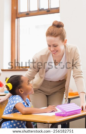 Teacher and pupil working at desk together at the elementary school - stock photo