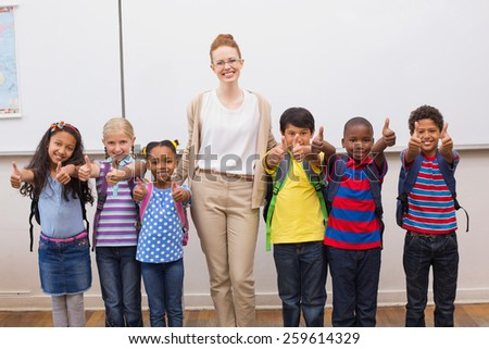 Teacher and pupils smiling at camera in classroom at the elementary school - stock photo