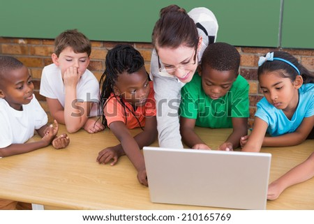 Teacher and pupils working at laptop at the elementary school - stock photo