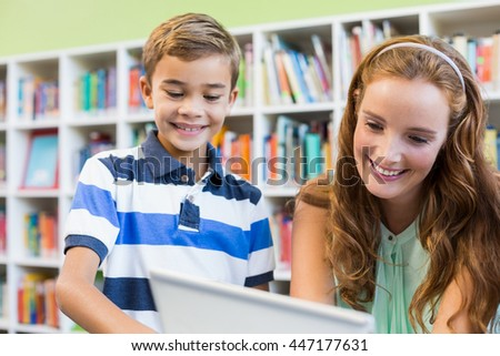Teacher and school boy using laptop in library at school - stock photo